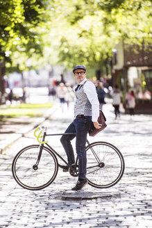 Mature businessman on bicycle in the city - HAPF01778