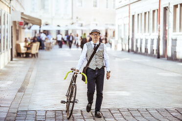 Mature businessman pushing bicycle in the city - HAPF01781
