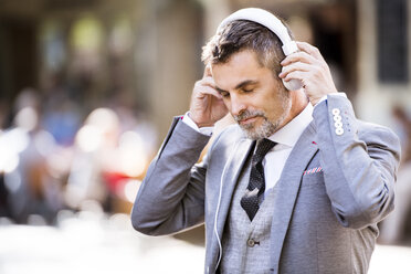 Mature businessman with headphones in the city - HAPF01784