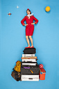 Confident flight attendant standing on pile of luggage - BAEF01371