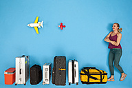 Woman waiting with row of luggage - BAEF01380