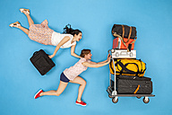 Friends pushing luggage trolley, hurrying for departure - BAEF01386