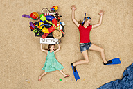 Mother and daughter running to the sea, carrying beach equipment on the head - BAEF01401