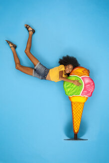 Young woman holding onto big icecream cone - BAEF01497