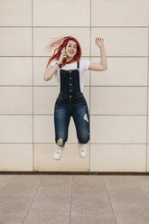 Redheaded woman on the phone jumping in the air - JPF00234