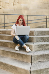Redheaded woman sitting on stairs using laptop and earphones - JPF00240
