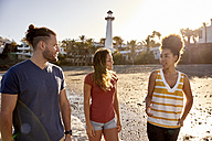 Spain, Canary Islands, Gran Canaria, three friends strolling on the beach at evening twilight - PACF00014