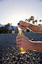 Man's hands opening beer bottle on the beach - PACF00029