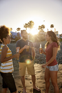 Three friends drinking beer on the beach at sunset - PACF00032
