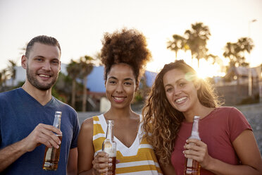 Group picture of three friends with beer bottles on the beach at sunset - PACF00038