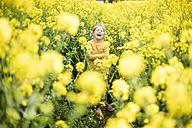 Laughing girl standing in rape field - MOEF00013