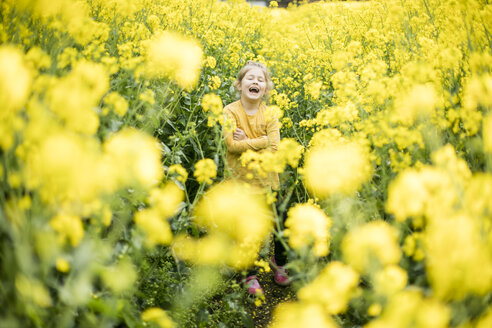 Laughing girl standing in rape field - MOEF00013