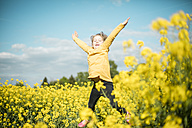 Carefree girl jumping in rape field - MOEF00016