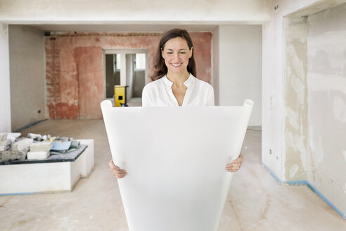 Smiling woman in empty apartment holding plan - DMOF00033