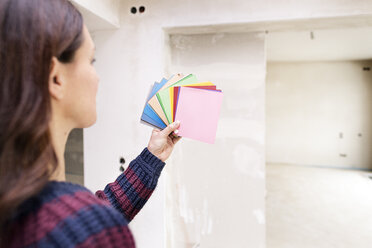Woman in new home choosing from color sample - DMOF00036