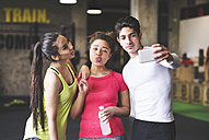 Three playful young people taking a selfie in gym - HAPF01795