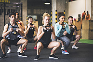 Group of young fit people lifting kettlebells in gym - HAPF01831