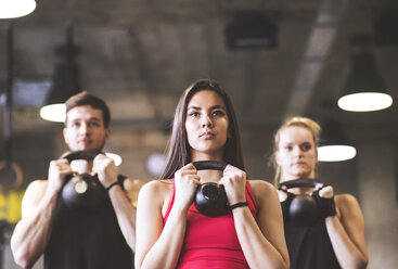 Confident young woman with training partners lifting kettlebell in gym - HAPF01834