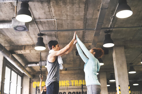 Two young athletes high fiving in gym - HAPF01837