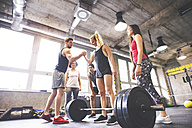 Group of young fit people motivating woman weightlifting in gym - HAPF01846