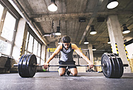 Young athlete exercising with barbell in gym - HAPF01849