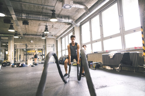 Young athlete exercising with ropes in gym - HAPF01855