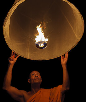 Thailand, Chiang Mai, Buddhist monk lighting lantern - TOVF00084