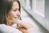 Smiling young woman looking out of the window - KNSF01640