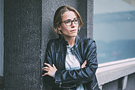 Young woman with glasses and leather jacket looking sideways - KNSF01649