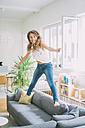 Excited young woman jumping on couch at home - KNSF01652