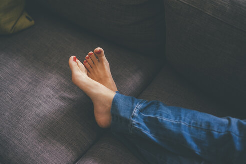 Feet of young woman lying on couch at home - KNSF01655