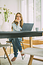 Portrait of young woman using laptop at home - KNSF01661