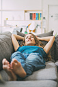 Smiling young woman lying on couch at home - KNSF01679