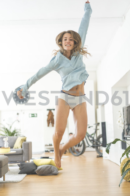 Excited young woman jumping at home - KNSF01691