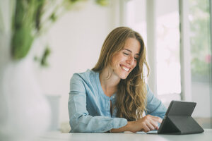 Smiling young woman using tablet at home - KNSF01694