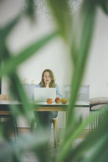 Young woman with closed eyes sitting at table with apples and laptop - KNSF01700