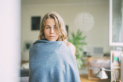 Portrait of young woman wrapped in a blanket - KNSF01703
