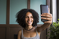 Happy young woman taking selfie in a coffee shop - ABZF02145