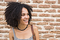 Portrait of smiling woman in front of brick wall - ABZF02157