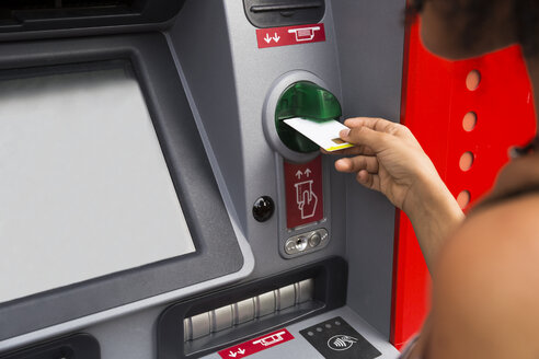 Woman pushing credit card at cash dispenser, partial view - ABZF02163