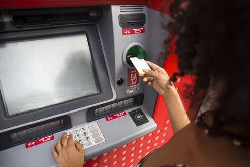 Woman pushing credit card at cash dispenser - ABZF02166