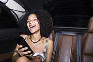 Portrait of laughing woman with smartphone sitting on the rear seats of a car - ABZF02169