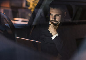 Businessman with laptop in car at night - UUF10879