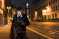 Stylish young man with tablet on urban street at night - UUF10885