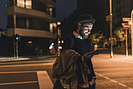 Stylish young man with tablet on urban street at night - UUF10888