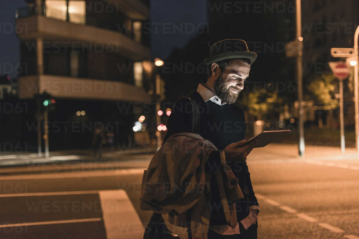 Stylish young man with tablet on urban street at night - UUF10888 - Uwe Umstätter/Westend61