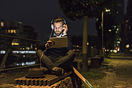 Young man with tablet and headphones in the city at night - UUF10891