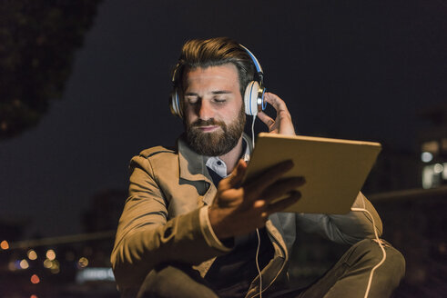 Young man with tablet and headphones in the city at night - UUF10894