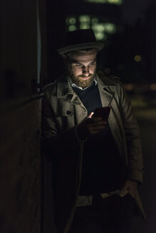 Stylish young man with cell phone in the city at night - UUF10897