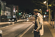 Stylish young man with cell phone on urban street at night - UUF10900